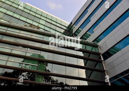 Abstract esterno di vetro di un ufficio moderno edificio nel centro di Singapore con pattern simmetrici, riflessioni e prospettive come sfondo astratto Foto Stock