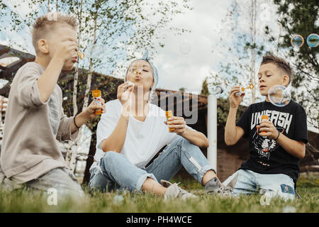 Close up della famiglia soffiare bolle all'aperto nel parco. Foto Stock
