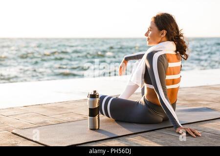 Immagine della giovane e bella donna fitness all'aperto sulla spiaggia hanno un resto seduta con asciugamani e acqua. Foto Stock