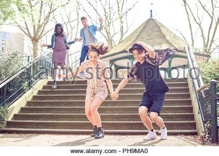 Amici di adolescenti saltare giù passi in posizione di parcheggio Foto Stock