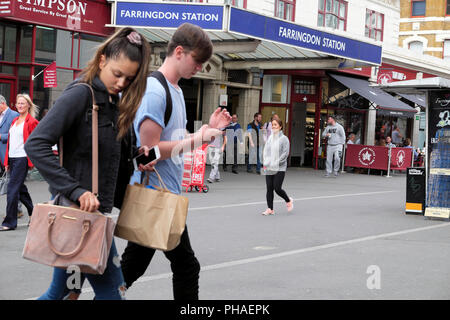 Una giovane donna giovane con le borse della spesa borsetta e telefono mobile a piedi in strada al di fuori della stazione di Farringdon in Clerkenwell, Londra UK KATHY DEWITT Foto Stock
