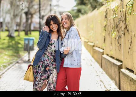 Due lieti di donne giovani amici abbracciando in strada. Bionda e bruna le  ragazze che 3a51956aa3d8