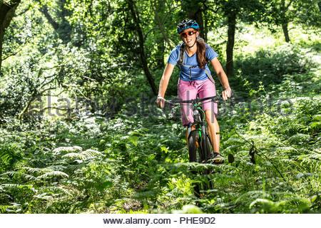 Woman mountain bike nella Foresta Foto Stock