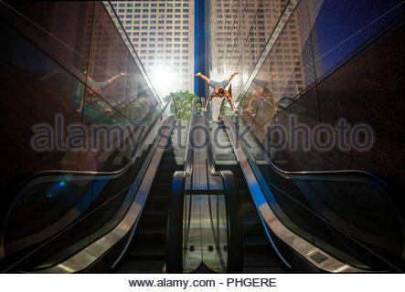 Shirtless uomo facendo handstand su escalator Foto Stock
