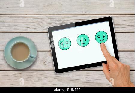La soddisfazione del cliente feedback questionario di indagine con la mano la scelta di smiley Foto Stock