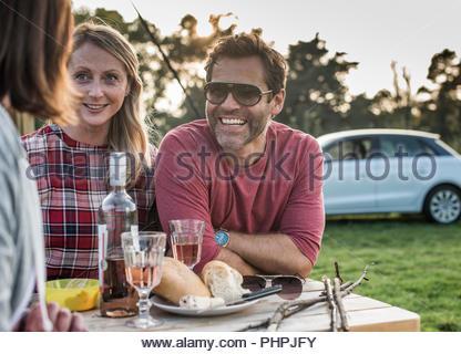 Persone sorridenti al tavolo da picnic Foto Stock