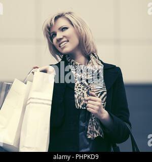 Felice moda giovane donna con le borse della spesa in strada di città Foto Stock