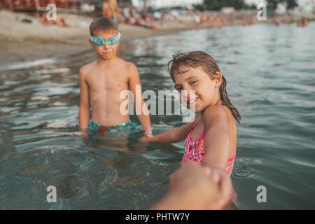 Dei bambini felici giocando in mare. I bambini si tengono per mano e invitare la loro madre per andare con loro. La vacanza estiva e uno stile di vita sano concetto Foto Stock