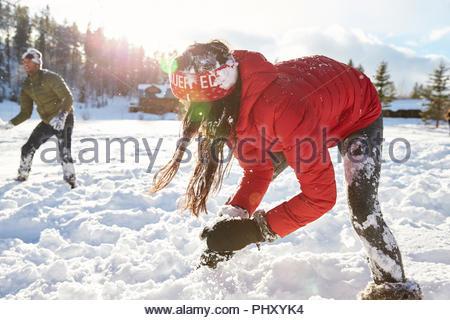 Coppia giovane avente lotta con le palle di neve Foto Stock