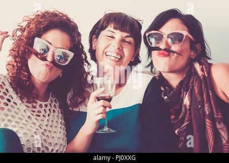 Tre femmine caucasica amici stare insieme in amicizia e follia usando i capelli come baffi e felicità il concetto di relazione. vintage c pieno Foto Stock