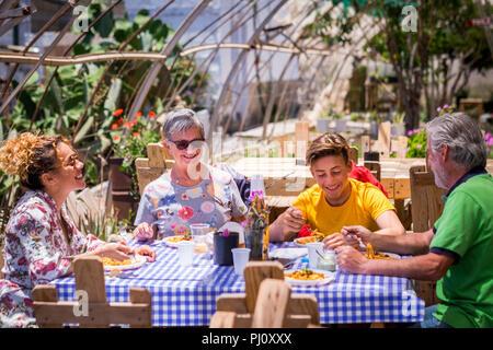 Allegro e felice famiglia in alternativa di un ristorante esterno tutti naturali e riciclata con pallet in legno. Bella la popolazione caucasica in attività per il tempo libero Foto Stock