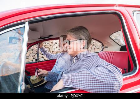 Nizza adulto giovane abbraccio e l'amore all'interno di un vecchio rosso vintage auto parcheggiate sulla strada. sorrisi e divertirsi viaggiando insieme. la felicità e lifestyle per ni Foto Stock