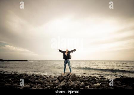 Indie caucasico giovane donna in piedi con le braccia aperte e godersi la natura e la libertà da solo sulle rocce in spiaggia. oceano in background. caldo fi Foto Stock
