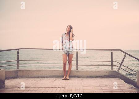 Giovane e bella signora caucasian woman standing in spiaggia sulla strada ascolto di musica con cuffie e godersi il tempo libero attività. vacanza e Foto Stock
