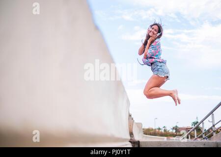 Concetto di felicità con la giovane bella ragazza jumping con gioiosa contro un cielo bianco sfondo blu. lato mare luogo. Allegra donna caucasica un sorriso Foto Stock