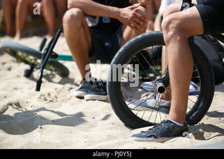 Giovani BMX motociclista seduto in bicicletta nel parco all'aperto in estate extreme sports festival. Adolescente ragazzo corse in bicicletta specializzata per eseguire trucchi