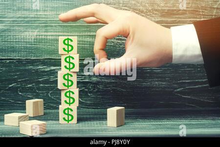 Imprenditore rimuove un cubo con una foto di dollari. crisi finanziaria ed economica in deflusso di capitali. il sabotaggio dell'economia. fallimento. Pressione sul Foto Stock