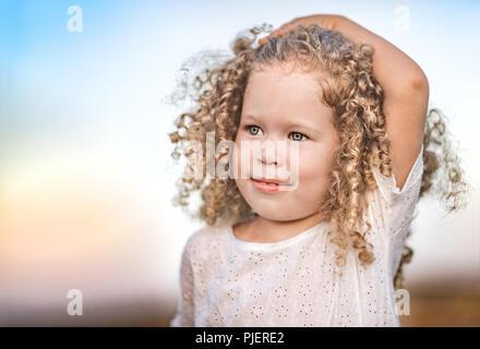 ... Outdoor ritratto di un sorridente bambina. Positivo il concetto di  emozione. Foto Stock 07f90b7fd37