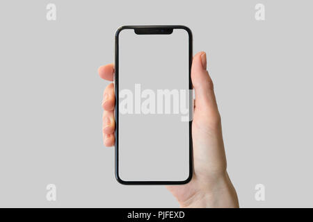 Mano che tiene la mascherina-free / cornice dello smartphone moderno di fronte a uno sfondo neutro Foto Stock