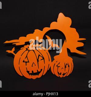 Halloween decorazione di sfondo il concetto di vacanza. Due zucche arancione visi arrabbiati ombra e silhouette su sfondo nero Foto Stock