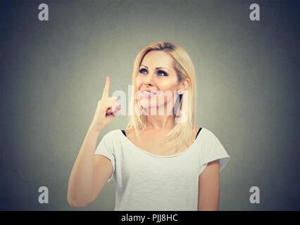 Ritratto di una donna informale tenendo un dito avente brillante idea su sfondo grigio