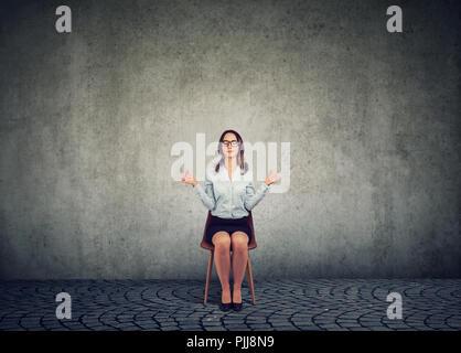 Business Woman in bicchieri seduti su una sedia e tenendo le mani distanti nella meditazione e armonia mantenendo gli occhi chiusi. Foto Stock
