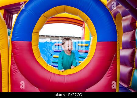 Funny bambino ride molto durante la riproduzione sul trampolino Foto Stock