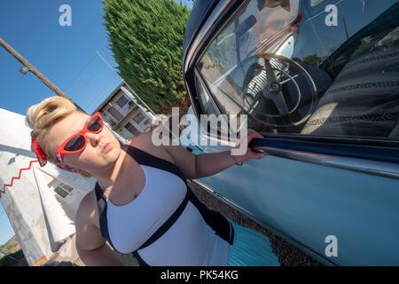 Bionda femmina adulta con un degli anni cinquanta vintage pin up acconciatura sorge nelle vicinanze di un abbandono auto d'epoca, indossando occhio di gatto occhiali da sole Foto Stock