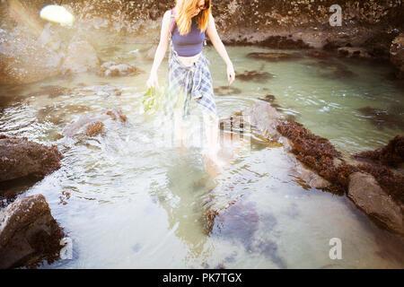 Donna che cammina in poco profonde acque dell'oceano Foto Stock
