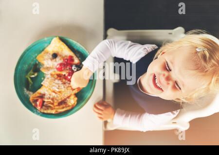Carino divertente bambina mangiare frittelle con frutti di bosco Foto Stock
