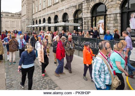 Persone in piedi in linea al di fuori del vecchio edificio della Biblioteca in attesa di entrare nel Libro di Kells Exhibition, il Trinity College di Dublino, il Leinster, Irlanda Foto Stock