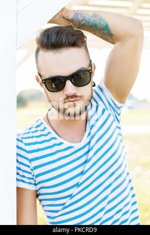 Bello hipster uomo in occhiali da sole con un tatuaggio sulla spiaggia in una giornata di sole Foto Stock