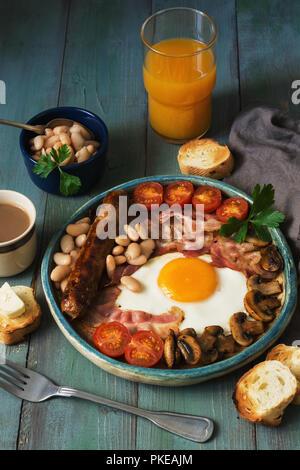 La completa prima colazione Inglese con uova strapazzate, salsicce, funghi, fagioli e pancetta su un rustico in legno tavolo verde Foto Stock