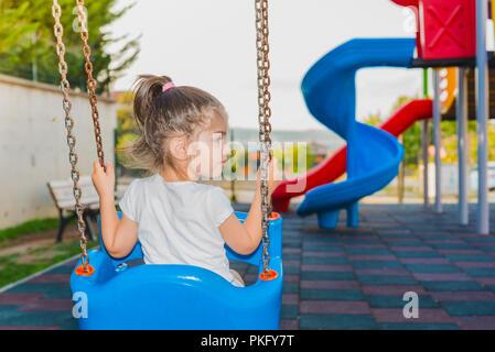 Vista posteriore di una incantevole piccola ragazza con sedie ed oscillante sul parco giochi Foto Stock