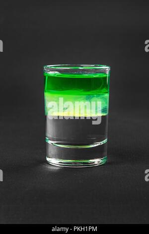 Variopinti cocktail stratificato, con vetro trasparente e colorato con bevanda al gusto di menta, banana, limone, assenzio, alcolico, vista laterale isolato Foto Stock