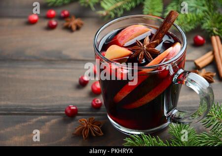 Natale vin brulé con Apple e mirtilli rossi. Concetto di vacanza decorate con rami di abete, mirtilli e spezie. Foto Stock