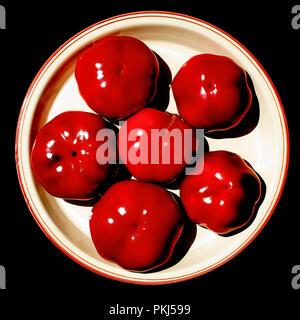 Still Life foto: alto contrasto di peperoni rossi sulla piastra bianca, con sfondo nero... i tre colori dell'alchimia. Foto Stock