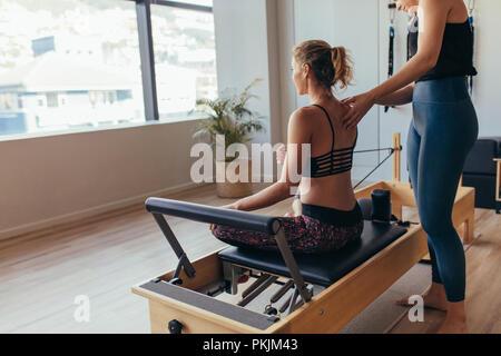 Donna seduta su pilates formazione macchina e tirando la fascia elastica. Pilates trainer aiutando una donna con il suo allenamento in palestra. Foto Stock