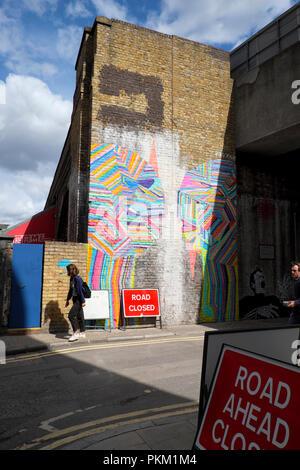 Giovane donna a camminare lungo i graffiti sulla parete del building a New Inn cantiere, Shoreditch East London REGNO UNITO KATHY DEWITT Foto Stock