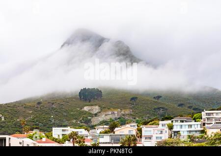 Il cloud e la nebbia copriva la Montagna della Tavola dietro le case di Camps Bay, Sud Africa Foto Stock