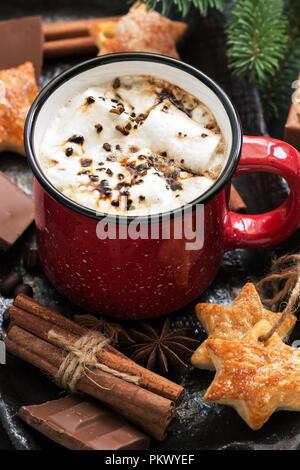 La cioccolata calda con marshmallow in una tazza rossa close-up, cannella, biscotti, cioccolato e rami di abete rosso. Natale. Messa a fuoco selettiva Foto Stock