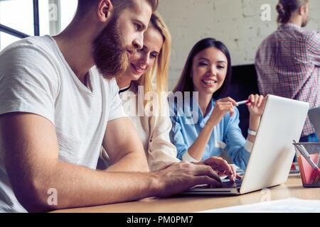 Bella gente di affari l'utilizzo dei gadget, studiando i documenti, parlando e sorridendo mentre si lavora in ufficio. Foto Stock