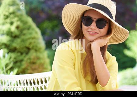 Colpo di Testa del giovane e bella donna che indossa gli occhiali da sole e cappello di paglia seduti all'aperto e rilassante. Foto Stock