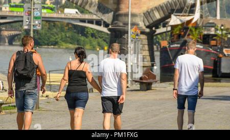 Quattro giovani a piedi lungo un sentiero lungo il fiume Vltava nel centro di Praga. Foto Stock