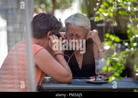 RIGA, Lettonia - 31 luglio 2018: Nella outdoor cafe, due donne anziane ascolta al telefono e grido. Foto Stock