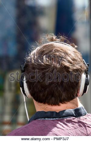 Giovane uomo seduto al sole con oltre le cuffie auricolari, Newbury, Inghilterra, Berkshire, Regno Unito Foto Stock
