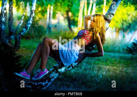 Teen ragazza mattina presto in boschi natura foresta che giace su albero inclinato splendido e spettacolare colore eccezionale impressionante sbalorditivo Foto Stock
