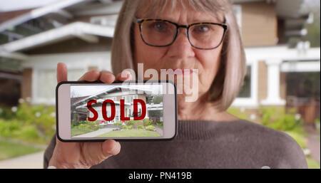 Anziana donna bianca tenendo il telefono con foto della casa che è stata recentemente venduta Foto Stock