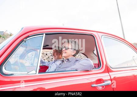 Nizza adulti caucasici senior paio di divertirsi e di amore all'interno di un vecchio rosso vintage auto parcheggiate sulla strada. sorrisi e godetevi il viaggio insieme. la felicità di un Foto Stock