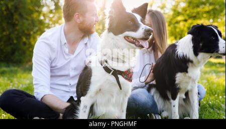Una giovane coppia a piedi un cane nel parco Foto Stock